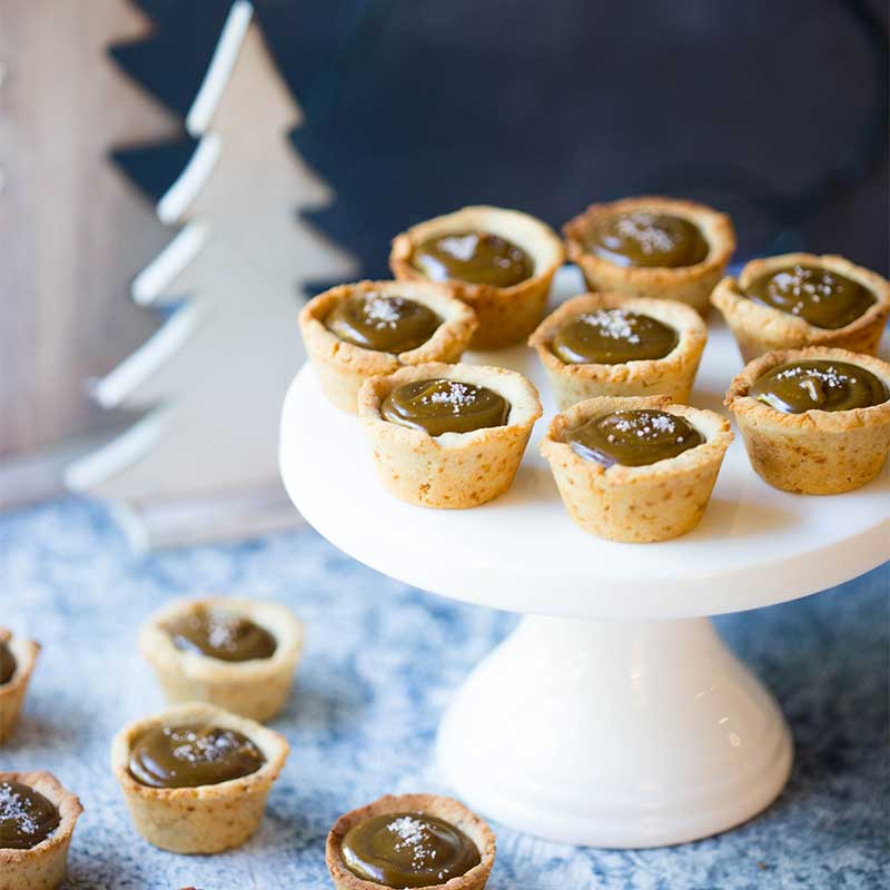 Salted caramel tarts on a cake stand next to Christmas decorations