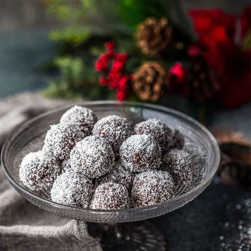 A plate of Chocolate Rum Truffles next to Christmas decorations
