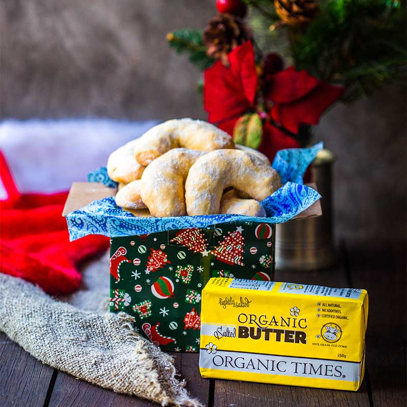 Greek Kourabiethes Biscuits next to Organic Times Salted Butter and Christmas decorations