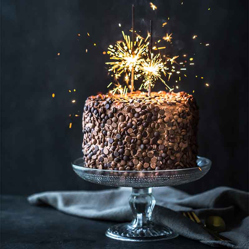 Sparkles on top of an Organic Times chocolate cake on a cake stand