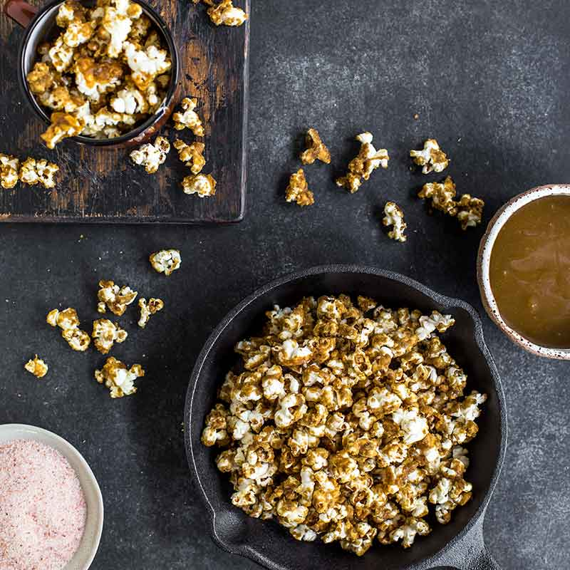 A bowl of caramel sauce next to a bowl of himalayan salt and a pan of caramel popcorn