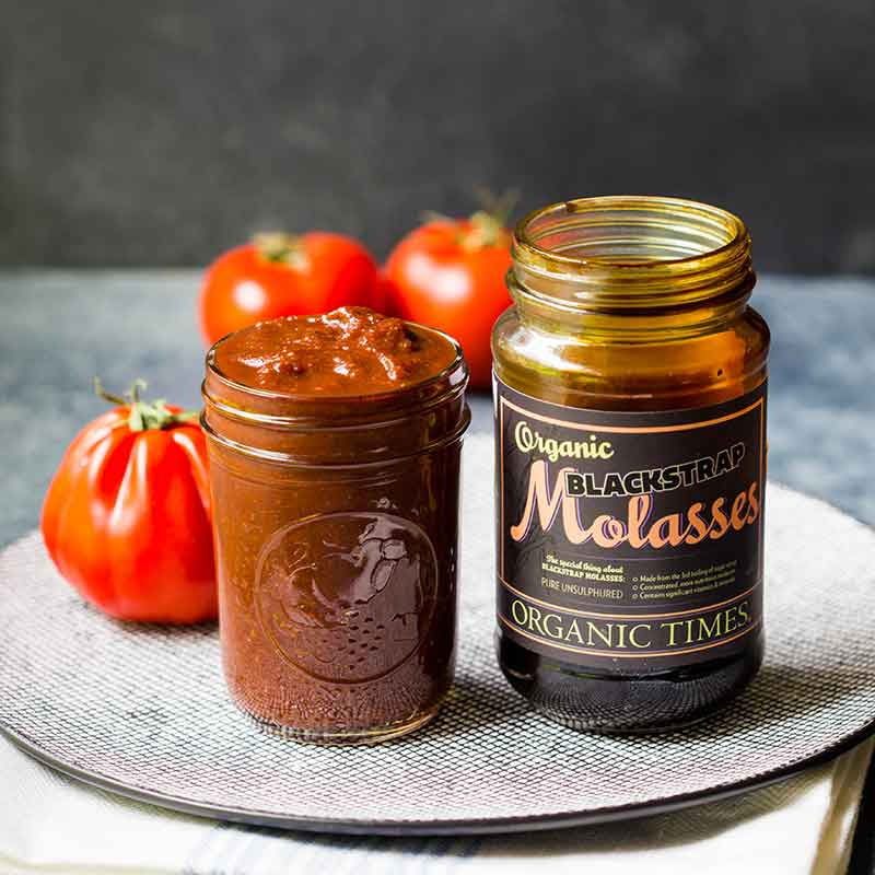 A jar of Organic Times Molasses next to a jar of homemade barbeque sauce and tomatoes