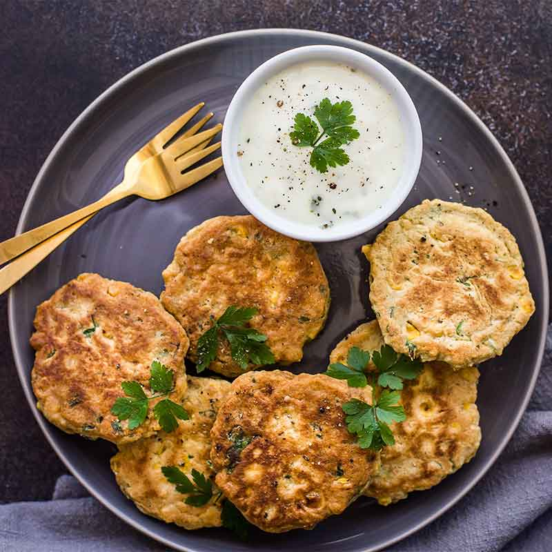 A plate of corn fritters with 2 forks and a dish of mayonaise