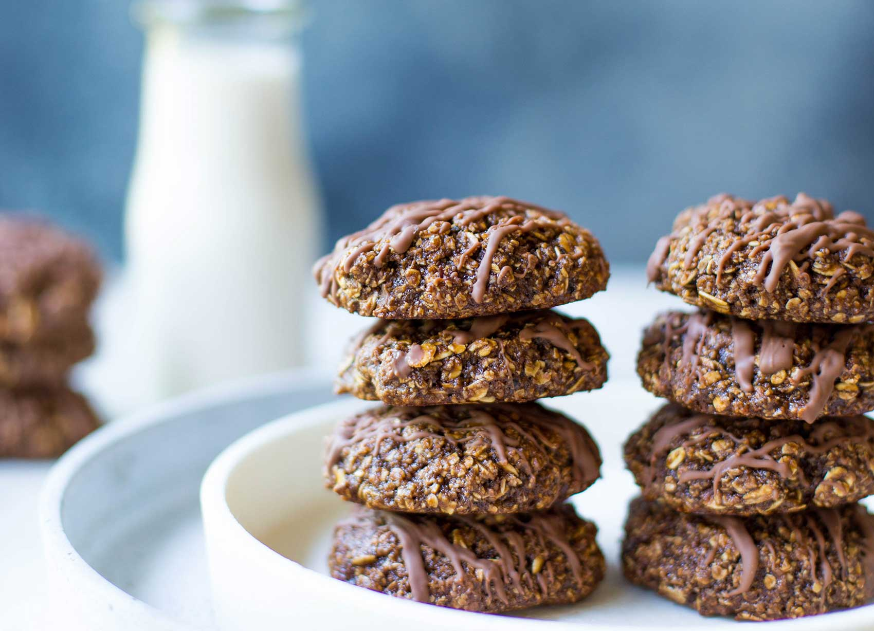 A stack of chocolate oat cookies with a bottle of milk