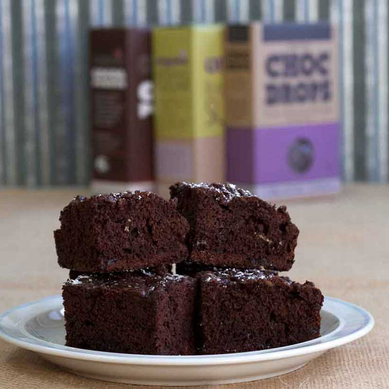 A plate of chocolate and zucchini brownies in front of Organic Times Pantry Ingredients