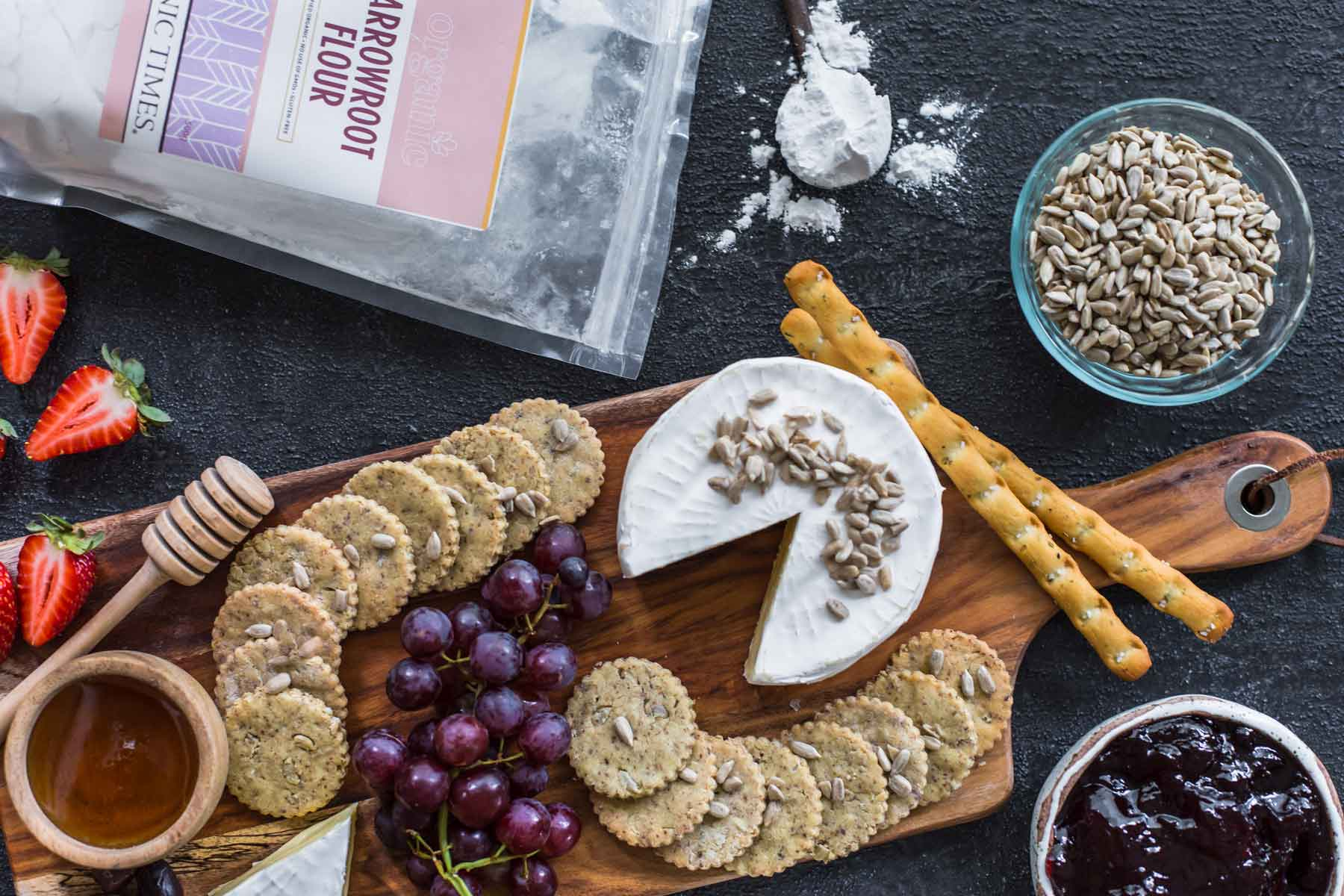 A bag of Organic Times Arrowroot Flour next to crackers, fruits, cheese, honey and olives