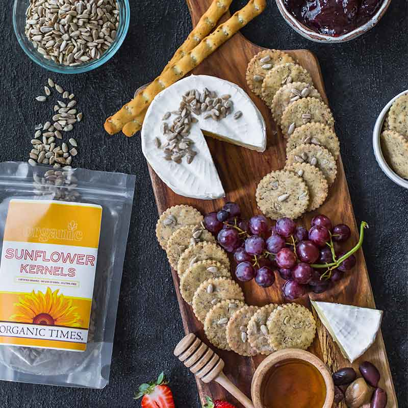 A bag of Organic Times Sunflower Kernels next to crackers, fruits, cheese, honey and olives