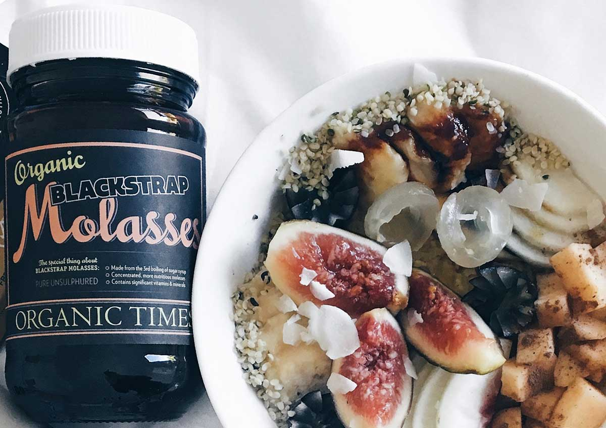 Organic Times Molasses next to a bowl of oatmeal topped with fruits and seeds
