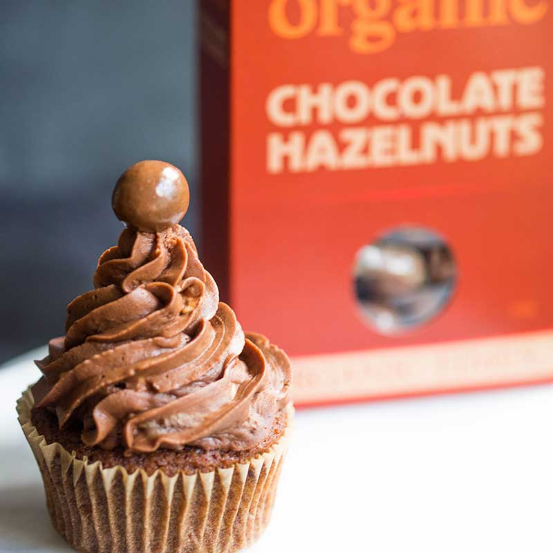 A box of Organic Times Hazelnut Chocolates next to a cupcake