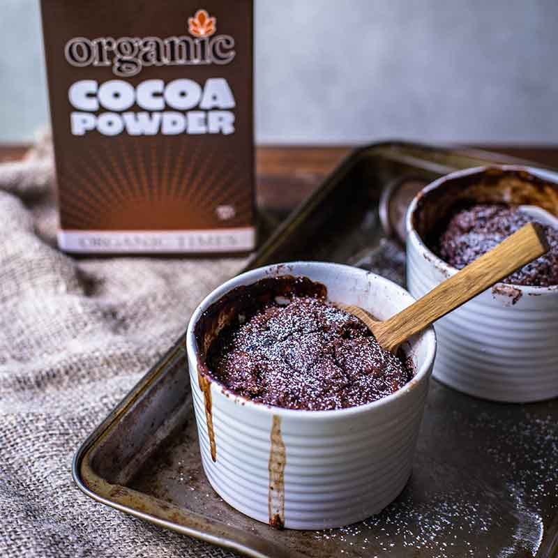Box of Organic Times Cocoa Powder next to chocolate self-saucing pudding
