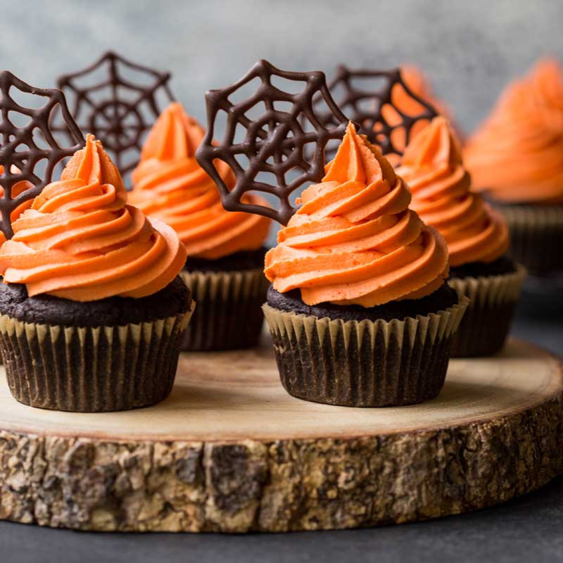 Halloween themed cupcakes on a wooden tray