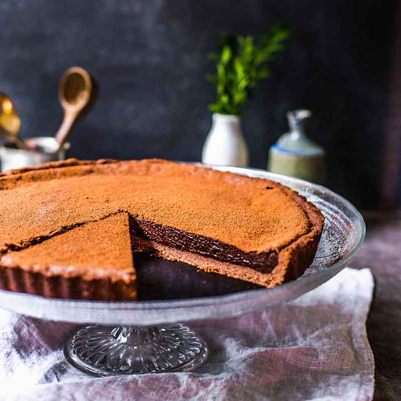 An organic chocolate tart with kitchen items in background