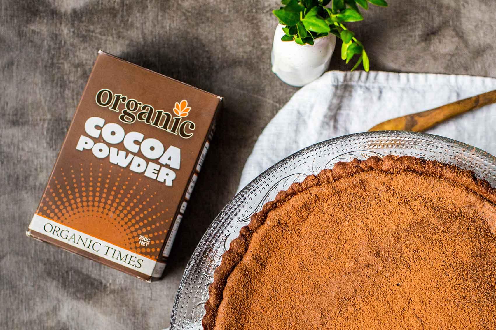 Organic Times Cocoa Powder next to a chocolate tart