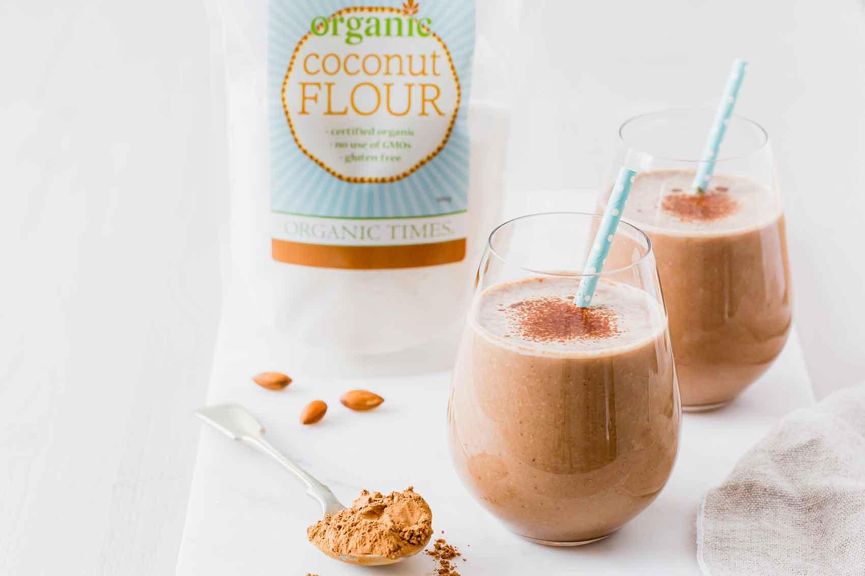 organic times coconut flour next to two glasses of carob banana almond smoothie