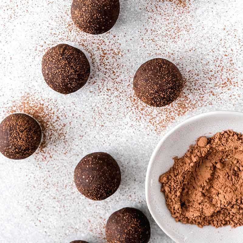 a bowl of carob powder with bliss balls next to it