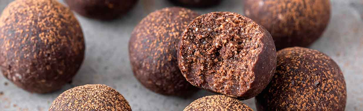 close up of a carob bliss ball with a bite taken out