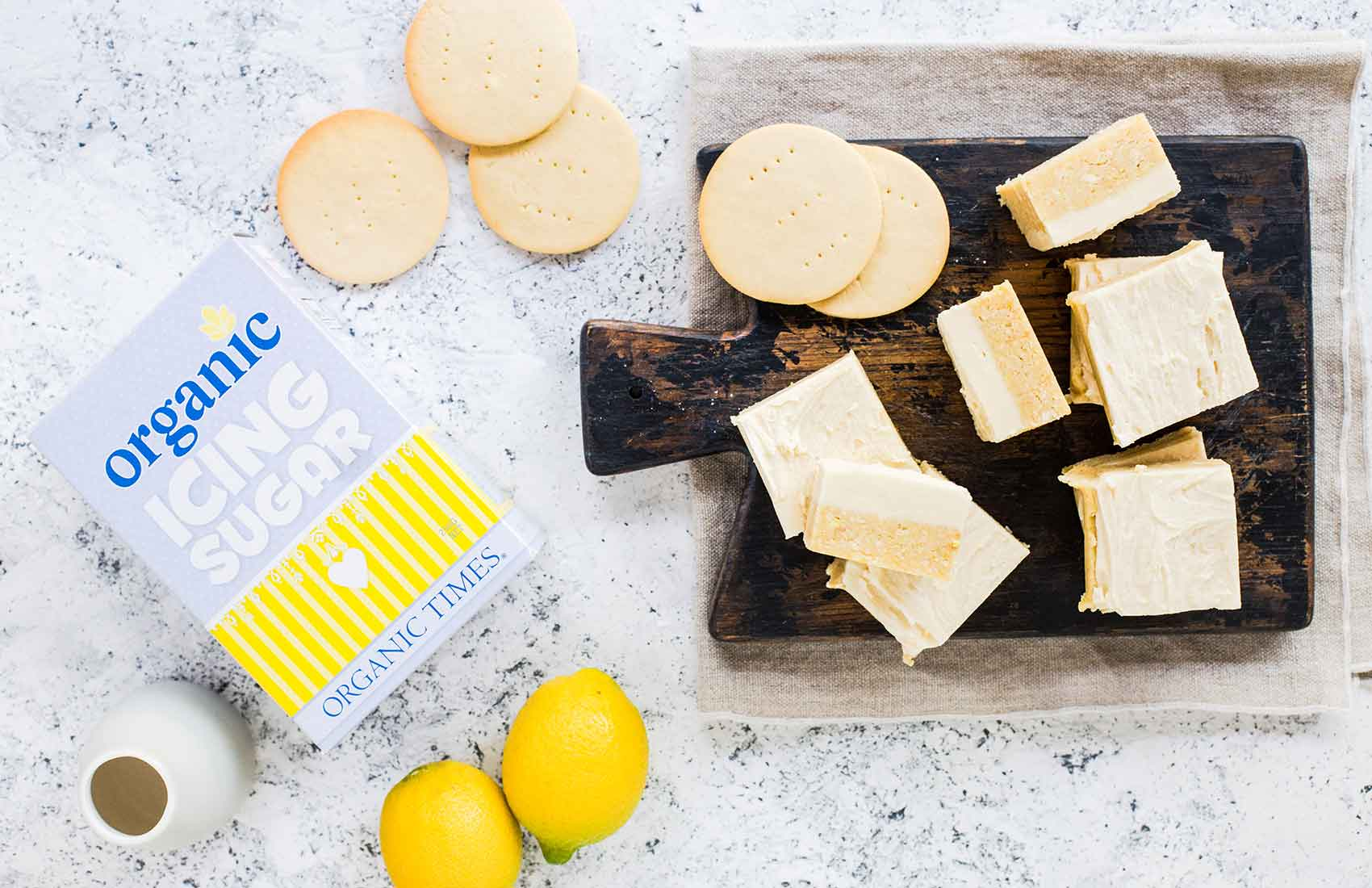 lemon slice pieces and arrowroot biscuits next to organic times icing sugar