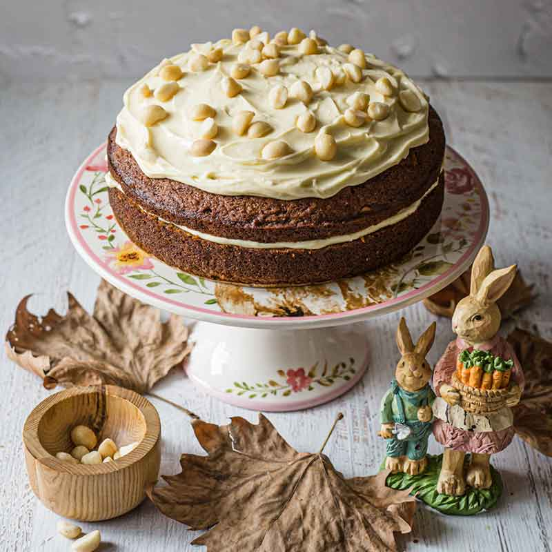 an Easter carrot cake on a cake stand with autumn leaves and bunny statues
