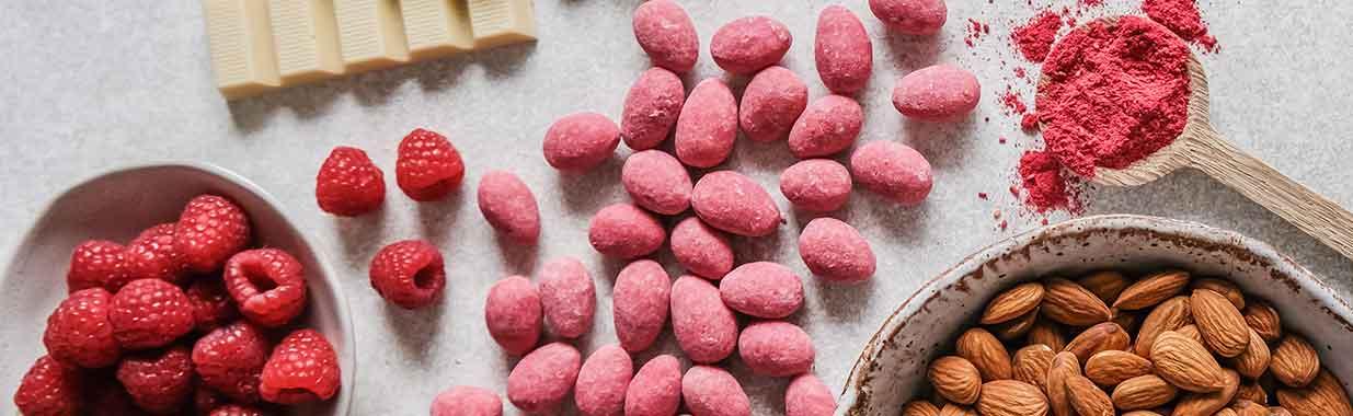 Organic pink almonds next to raspberries and white chocolate